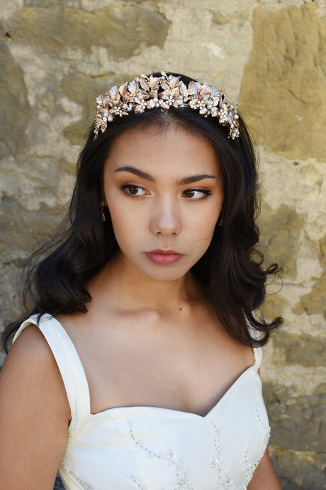 Bridal Model wears a pale rose gold tiara in her dark hair standing against an old stone wall