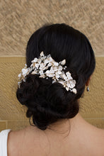 Load image into Gallery viewer, A dark haired bride wears a gold flowers headpiece at the back of her head with a stone wall background
