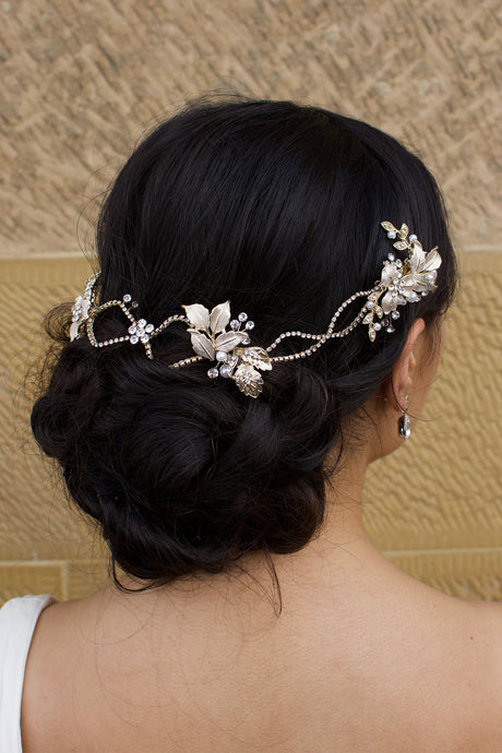 A dark haired model with curly hair wears a pale gold bridal vine at the back of her head