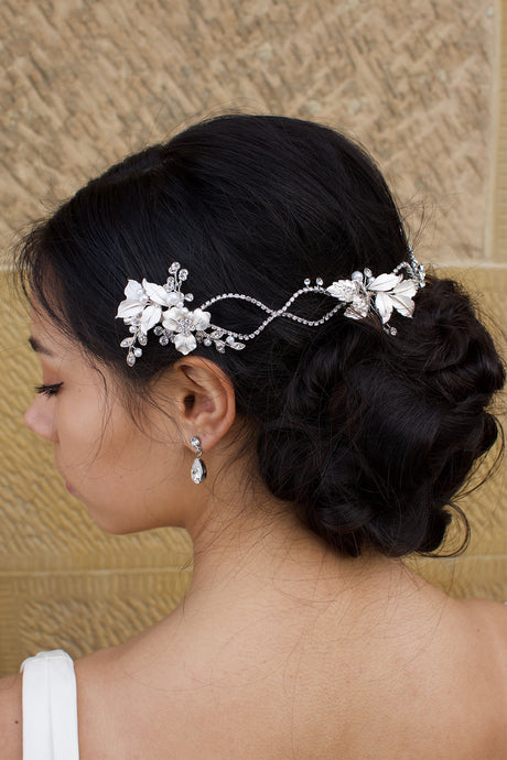 A dark haired model with curly hair wears a silver vine at the back of her head with stone background