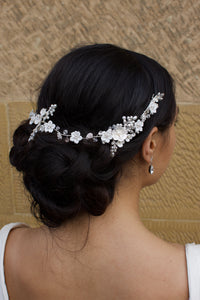 Silver and ceramic flower vine worn at the back of the head of a dark hair bride