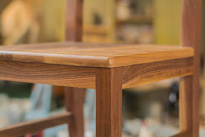 close up view of seat of chair stool with back in dark wood
