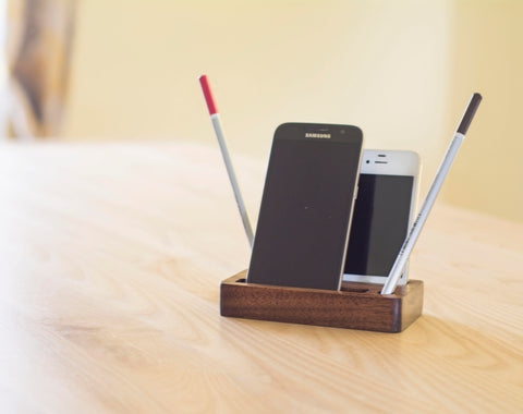 two iPhones in wooden holder with pencils on desk