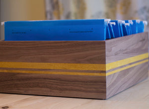 brown wood filing box with files and with yellow stripe