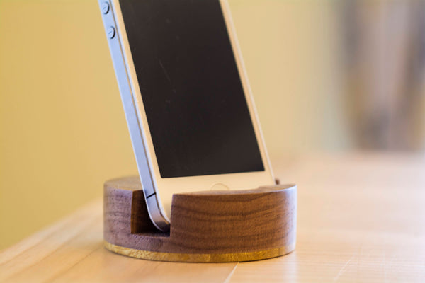 iPhone sitting in round wooden holder on desk
