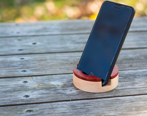 apple iPhone sitting in round wooden holder