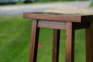 close up view of dark wood bar stool with square seat