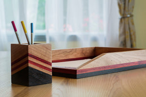 red striped wooden desk tray on desk with square wooden pencil holder