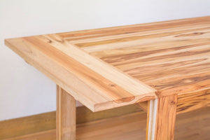 view of how wooden dining table extends with leaf
