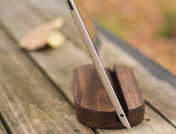 oblong wooden holder holding apple iPhone