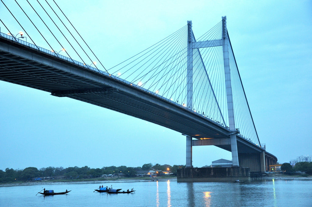 simple rowing boats with one oarsman under the Second Hooghly Bridge on the Hugli-Ganga river, Kolkata, at dusk