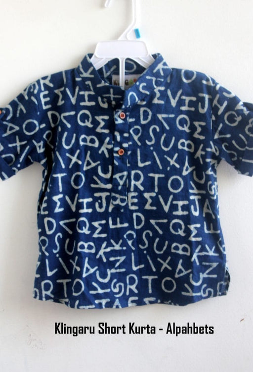 A navy blue short shirt/kurta with printed english alphabets is hanging on a hanger