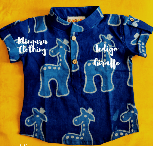 A little boy wearing an indigo blue kurta with giraffe motifs