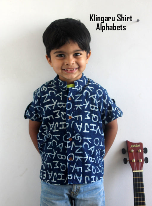 A little boy wearing a shirt with alphabets motifs