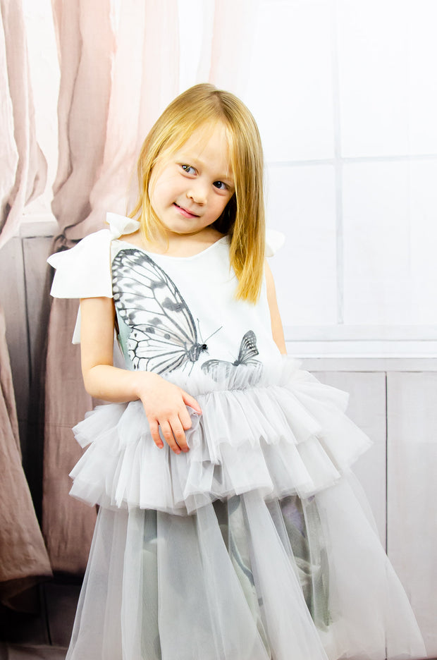 handmade short white flower girl's dress with a tulle skirt, ruffles at the waist and a butterfly patterns on the top