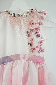 unique, handmade, blush pink baby girl flower girl dress in pink, with a tulle skirt, ribbon at the waist and 3D floral pattern