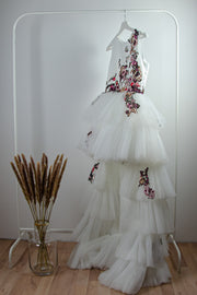 handmade long white flower girl dress with a multi-layered tulle skirt and pink and red floral embroidery