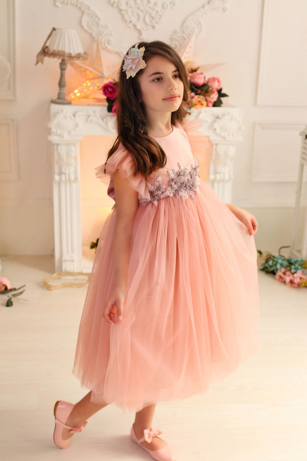 girl in pastel pink dress with multi-layer tulle skirt and floral embellishment