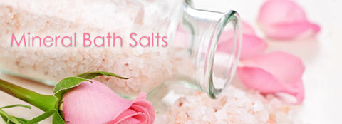 apothecary jar with bath salts spilling from it surrounding by soft pink roses