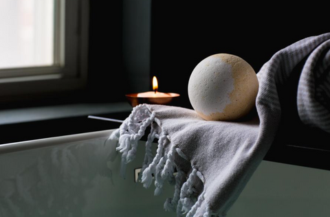 Planet Yum Milk & Honey Bath Bomb hovering over a hot bath with a glowing candle nearby