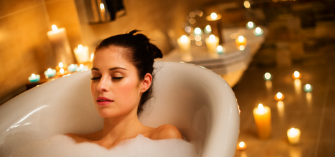 woman in bath relaxing with lots of candles
