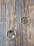 Personalized birthstones suspended in gold hexagon