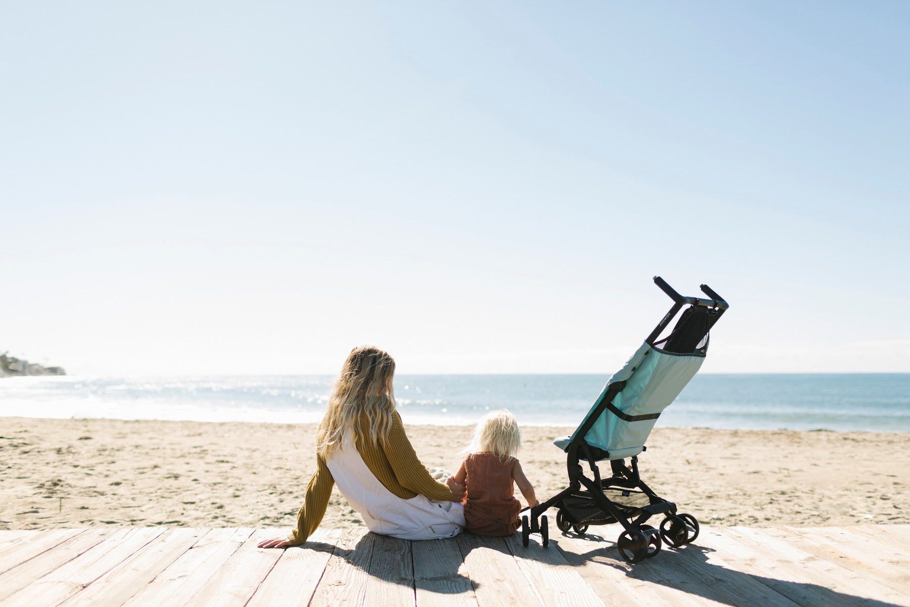 Leah on the beach with daughter and the Poppy stroller