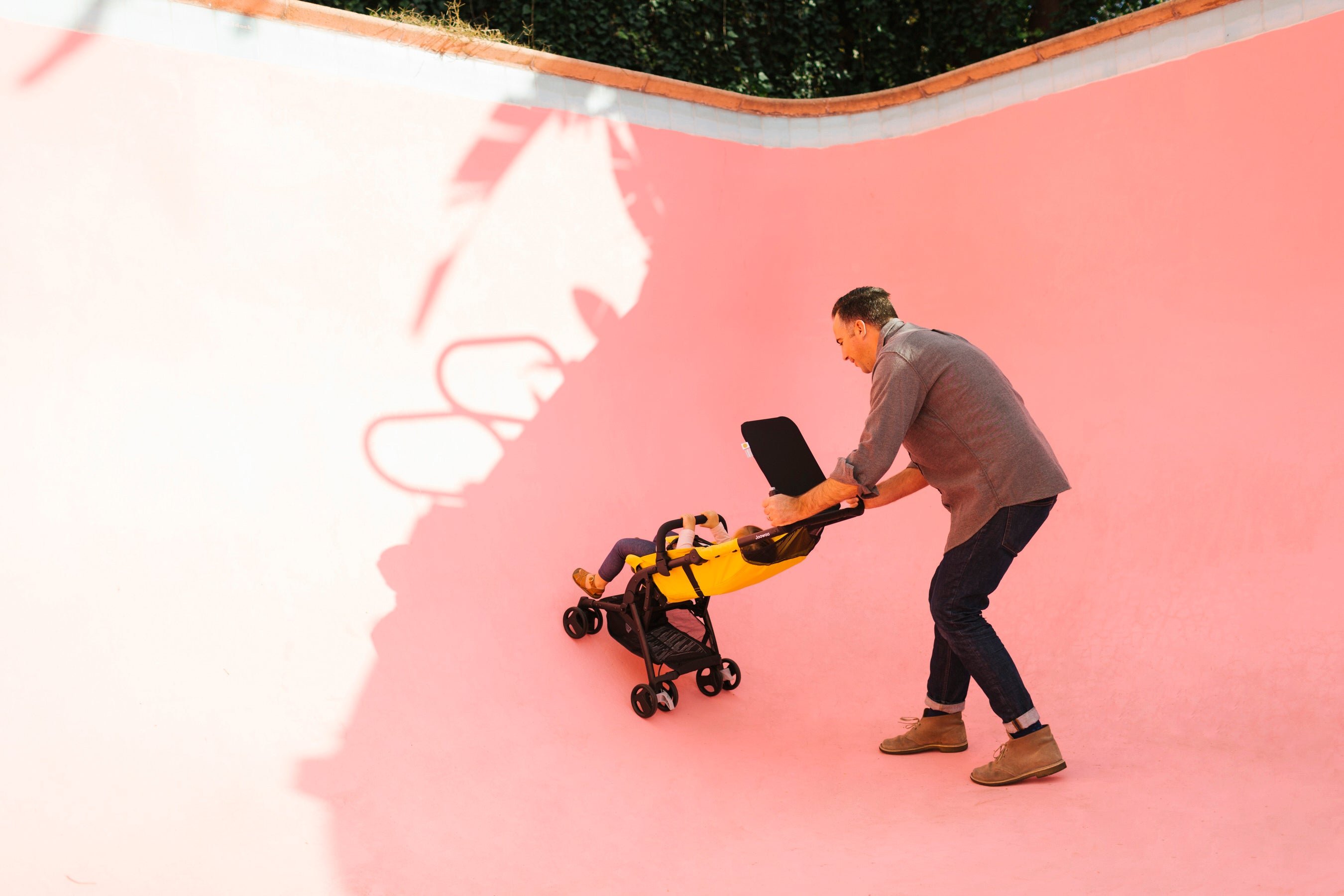 Eric pushes his daughter in their empty pink swimming pool.