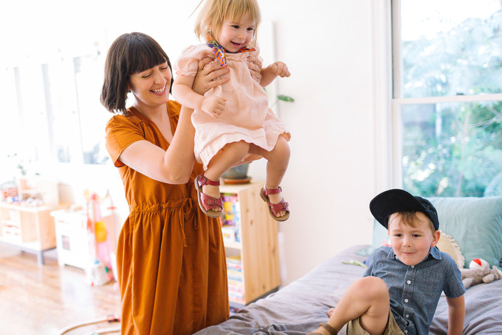 Erin Perez Hagstrom playing and laughing with her kids at home.