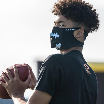 Black White Fang Play Safe Face Mask – Male Football Player Wearing Protective Safety Face Mask while Getting Ready to Throw Ball to a Receiver - Left Angle