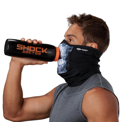Skull Play Safe Neck-Face Gaiter – Male Model Wearing Protective Safety Face and Neck Covering while Drinking a Hydration Water Bottle - Left Angle