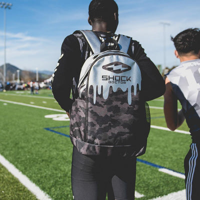 Youth Football Player Wearing Shock Doctor Premium Camo Drip Backpack
