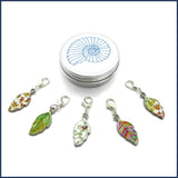 five colourful enamel leaf stitch markers with ammonite tin
