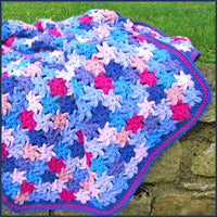 crochet flower blanket on a garden wall