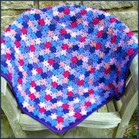 crochet flower blanket on a wooden bench