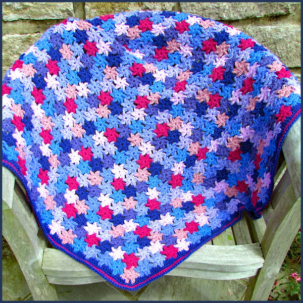 crochet flower blanket on a garden chair