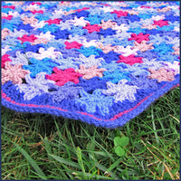 crochet flower blanket on grass