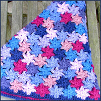 crochet flower blanket folded on a wooden bench