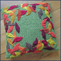 crochet cushion with leaf pattern on a wooden floor