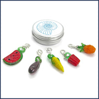 five glass fruit and vegetable clip-on stitch marker charms with an aluminium tin