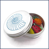 five glass fruit and vegetable clip-on stitch marker charms in an aluminium tin