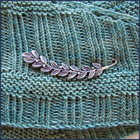 silver leaf and berries shawl pin on knitted fabric