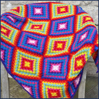 Mexican-inspired crochet blanket draped over a garden chair