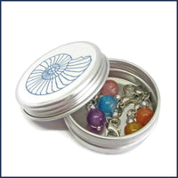 stone stitch markers in an ammonite tin