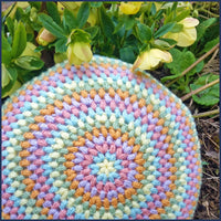 round crochet cushion with hellebores