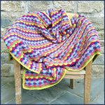 shell stitch crochet blanket on a garden chair