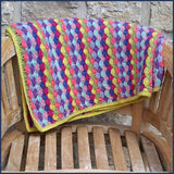 shell stitch crochet blanket folded on a garden chair