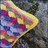 shell stitch crochet cushion against a stone wall