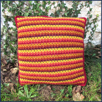 stripey crochet cushion against a garden wall
