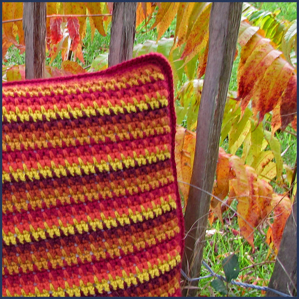 stripey crochet cushion against a wooden fence
